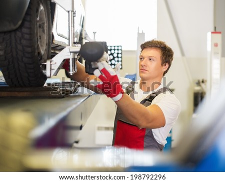Young serviceman checking wheel alignment  in a car workshop  - stock photo