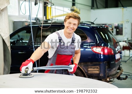 Young serviceman performing grinding with machine on a car bonnet in a workshop - stock photo