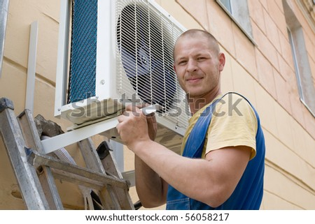 Young setup man installs the new air conditioner for office. - stock photo