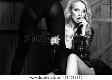 Young sexual attractive sensual couple of blond woman with long curly hair and back view of female beautiful legs in erotic panties and stocking in studio black and white, horizontal - stock photo