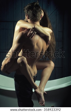 Young sexual passionale sensual couple of attractive flexible woman with beautiful naked body embracing handsome muscular man in jeans with legs in bathroom on wood backdrop, vertical photo - stock photo