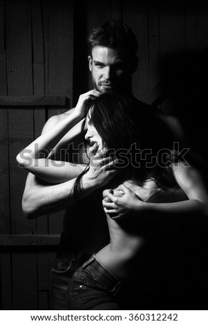 Young sexual undressed sensual attractive couple of handsome bearded muscular macho man touching and embracing passionate pretty woman with body and breast on studio background, vertical picture - stock photo