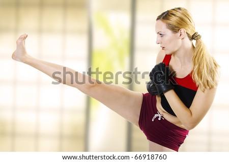 Young sexual woman fighter kick leg side. Fight. Martial art training - kickboxing; muay thai; taekwondo; Jiu-jitsu; kungfu or mma. - stock photo