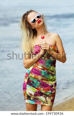 Young sexual woman sucking lollipop on water background. Lifestyle. - stock photo