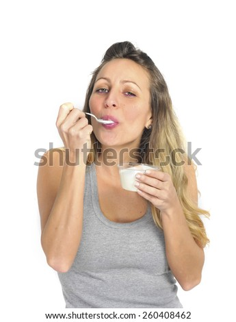 young sexy and attractive blond hair girl with spoon happy and fit eating natural cream yogurt in diet healthy nutrition and fitness concept isolated on white background - stock photo