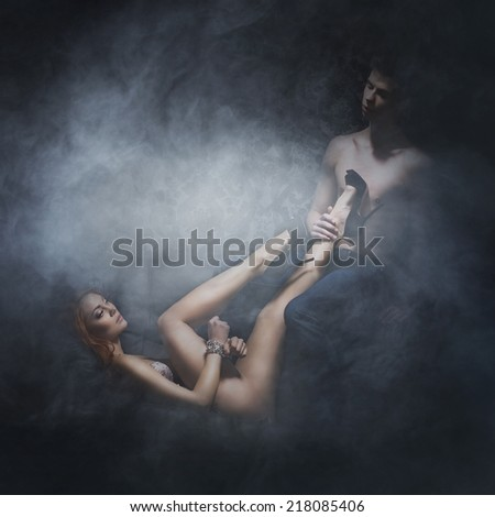 Young, sexy and beautiful couple hugging on the leather sofa at night over smoky background - stock photo