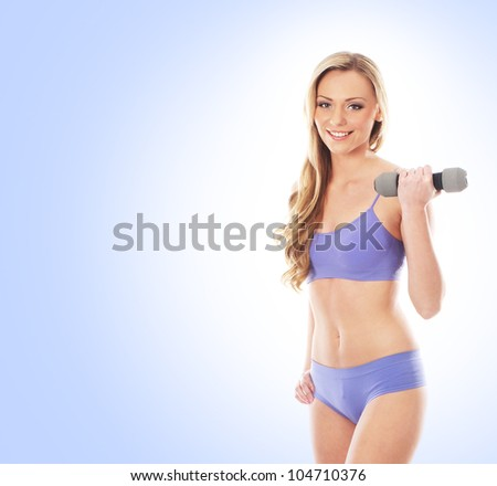 Young sexy and sporty woman over blue background - stock photo