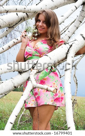 Young sexy beautiful girl between the branches