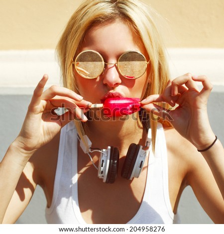 Young sexy blonde girl eating red ice cream in summer hot weather in round sunglasses and white earphones have fun and good mood looking in camera and smiling - stock photo