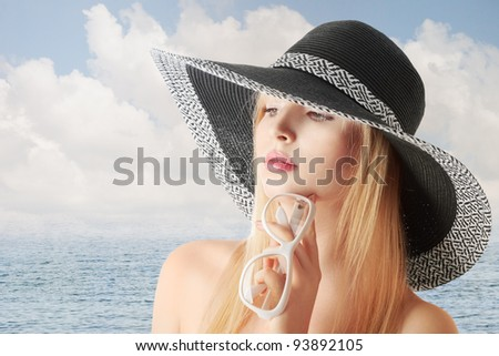 Young sexy blonde girl in sun-hat at sea beach looking sidewards - stock photo