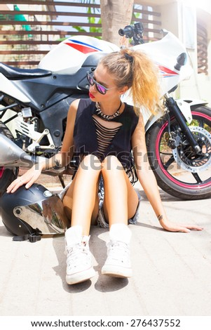 Young sexy blonde woman posing with helmet opposite motorbike.Lifestyle portrait bright toned colors,cool rock n roll girl,shows fashion wear summer outfit and bright summer sunglasses.Red lips - stock photo