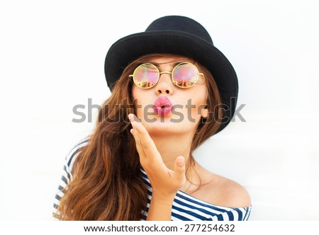 Young sexy blonde woman sending a kiss and posing in the white wall,wearing frock, swag hat,mirrored summer round sunglasses, bright summer make up,show happy emotions,Lifestyle bright toned colors.  - stock photo