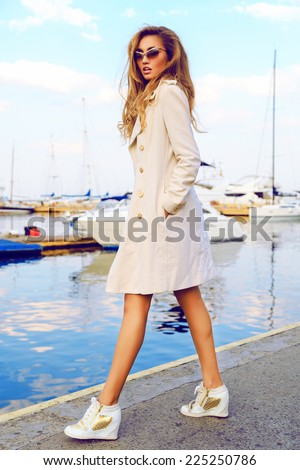 Young sexy blonde woman with long prefect legs posing at luxury yacht club, wearing trendy sneakers coat and golden sunglasses, great view on seaside and boats.