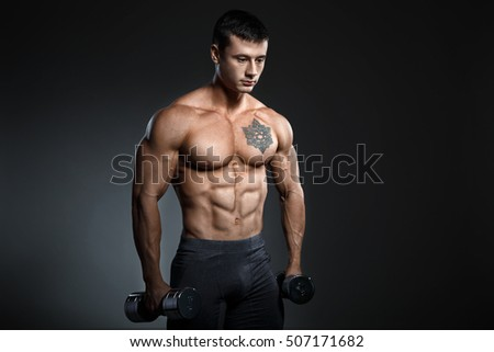 Young sexy bodybuilder with perfect body doing exercise with barbell on black background.  Strong man with muscle cubes on press. Sport concept image