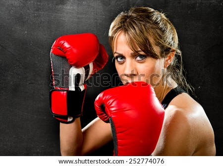 young sexy boxer sport girl with red boxing gloves posing on stance looking angry and dangerous isolated on black grunge studio background in female sport fitness concept - stock photo