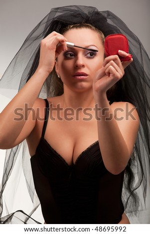 Young sexy bride using makeup - stock photo