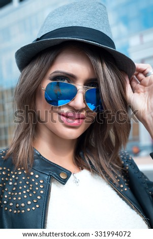 Young sexy brunette woman closeup portrait. Stylish woman posing on the street with interested look,wearing bike leather coat,grey hat and blue mirrored sunglasses.Perfect skin,big lips,blue eyes,  - stock photo