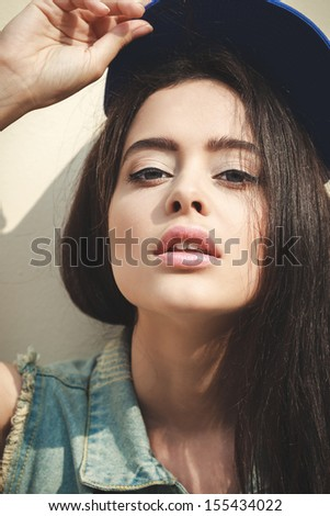 Young sexy brunette woman closeup portrait. Stylish woman posing with interested look and cap on her head. - stock photo