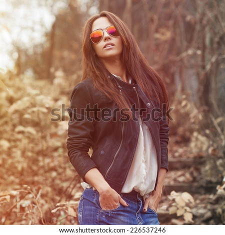 Young sexy brunette woman in jeans, jacket and sunglasses posing outdoor  - stock photo