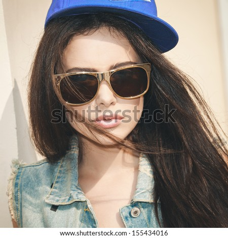 Young sexy brunette woman in sunglasses closeup portrait. Stylish woman posing with interested look  and  cap on her head. - stock photo