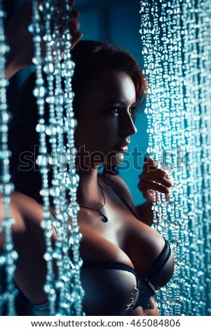 Young sexy brunette woman standing at glass curtains portrait. Dark night colors.