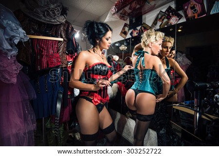 Young sexy cabaret female dancers at mirror in dressing room, backstage - stock photo