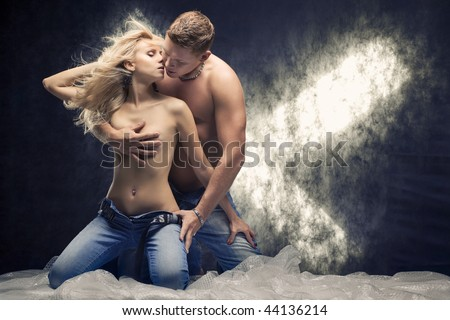 Young sexy couple in a studio. Toned - stock photo