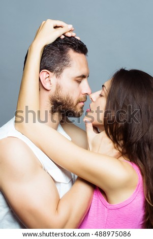young sexy couple of bearded handsome muscular man with beard and pretty woman or girl with long brunette hair embracing in studio on grey background