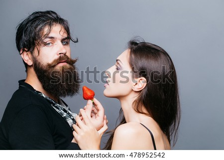 young sexy couple of woman with pretty face and brunette hair with bare shoulders and handsome bearded man with long beard eating red strawberry berry fruit in studio on grey background