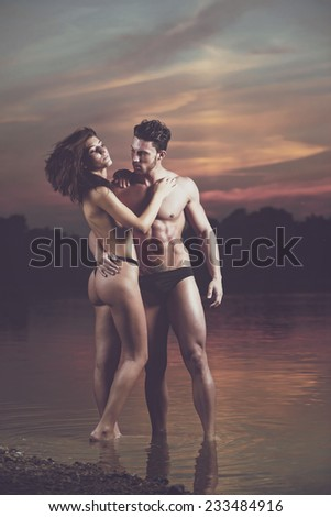 Young sexy couple on beach topless at sunset..Fashion colors. - stock photo
