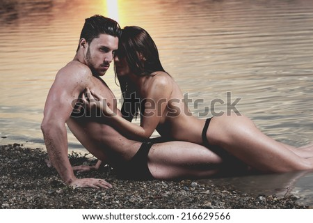 Young sexy couple on beach topless at sunset..Low light.  - stock photo