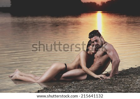 Young sexy couple on beach topless at sunset..Low light. Fashion colors. - stock photo