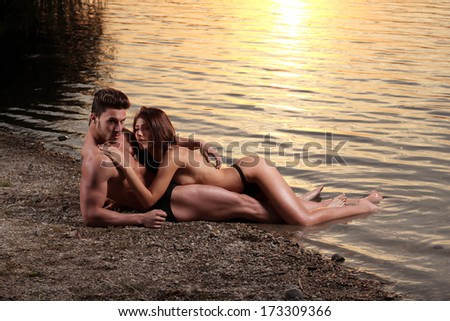 Young sexy couple on beach with sunset in background - stock photo