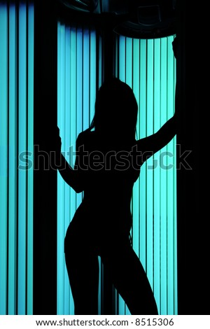 Young sexy female in a tanning cabin, shoot for shape against a light. - stock photo