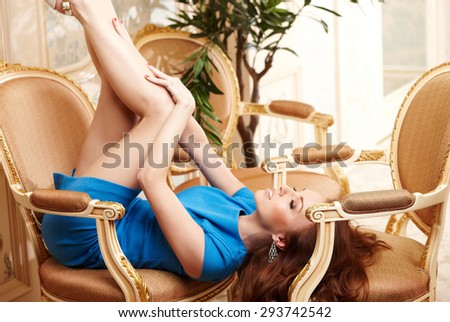 Young sexy female in short blue dress lying on vintage chairs with her legs up. - stock photo