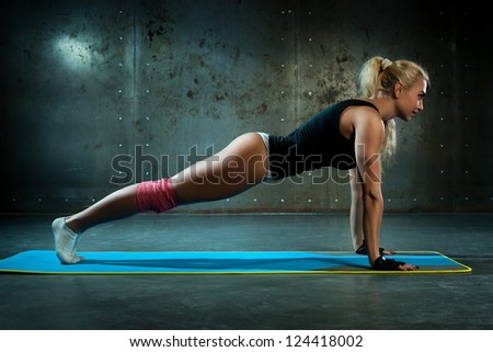 Young sexy fitness woman doing push-ups. - stock photo