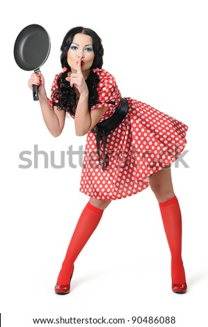 Young sexy girl in a polka dot dress with frying pan on white background, pinup concept - stock photo