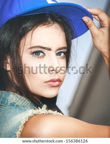 Young sexy girl in blue cap and jeans jacket .  Outdoors, lifestyle. - stock photo