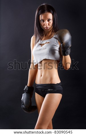 Young sexy girl over black background with boxing gloves