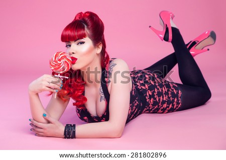 Young sexy girl, 50s style, posing with lollipop - stock photo