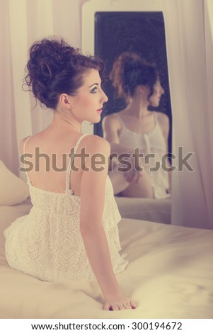Young sexy girl sits in front of the mirror in her bedroom. The reflection in the mirror. Boudoir fashion. - stock photo