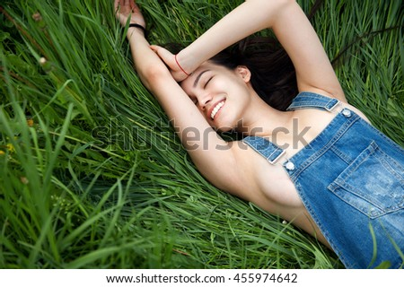 young sexy girl smiling on the green grass background  - stock photo