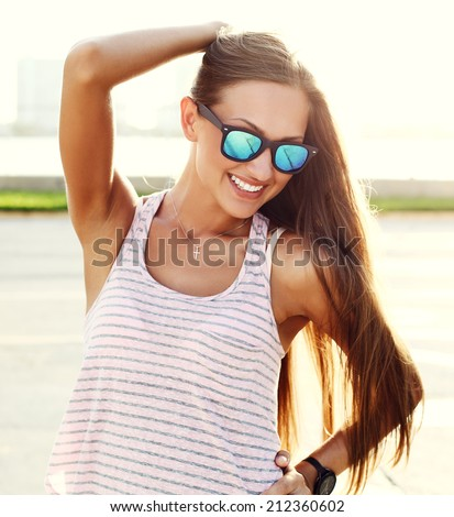 young sexy girl standing on the street over sunset wearing trendy sunglasses. - stock photo
