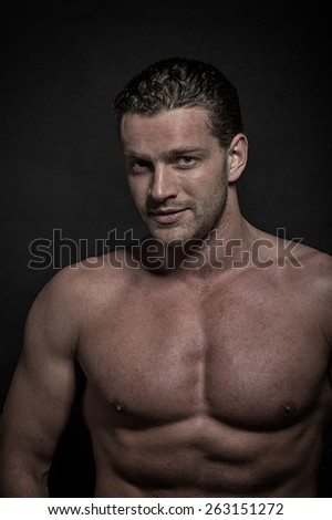 Young sexy handsome athletic man with naked torso on dark background  - stock photo