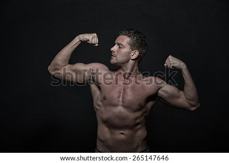 Young sexy handsome athletic man with naked torso on dark background, front view - stock photo