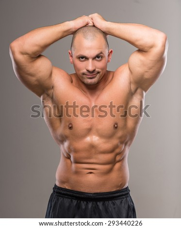 Young sexy handsome athletic man with naked torso on gray background.