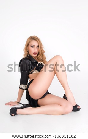 Young sexy lady in a mini skirt sit on the flour - stock photo