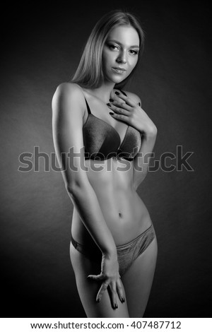 Young sexy lady in erotic lingerie over dark background - stock photo