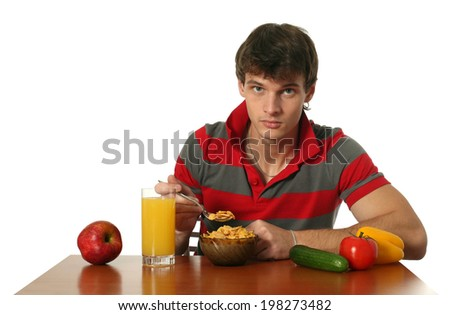 Young sexy man eating his breakfast isolated on white - stock photo