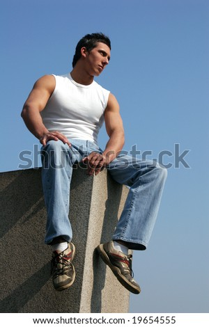 Young sexy man in a white tank top sitting on the stone blocks with blue sky behind